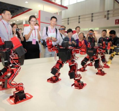"""BEIJING, CHINA - MAY 18:  (CHINA OUT) People look at dancing robots during the 14th China Beijing International High-tech Expo (CHITEC) at the China International Exhibition Center on May 18, 2011 in Beijing, China. The 14th CHITEC will be held in Beijing from May 17th to 22nd, 2011, with the theme of """"innovation driving development, science and technology leading transformation"""".  (Photo by ChinaFotoPress/Getty Images)"""