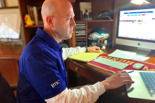 In this image provided by Jay Woods,  Woods, a Designated Market Maker with IMC and NYSE Floor Governor, who normally works on the New York Stock Exchange trading floor, works in his home office in Basking Ridge, N.J., Thursday, March 26, 2020. Stocks are surging again on Wall Street as a massive coronavirus relief bill gets closer to passing Congress. (Shannon Woods/Courtesy Jay Woods via AP)