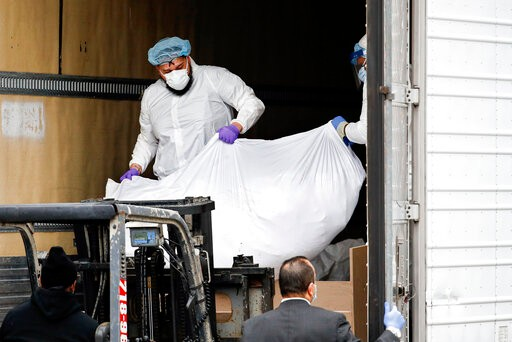 A body wrapped in plastic is loaded onto a refrigerated container truck used as a temporary morgue by medical workers wearing personal protective equipment due to COVID-19 concerns, Tuesday, March 31, 2020, at Brooklyn Hospital Center in Brooklyn borough of New York. The new coronavirus causes mild or moderate symptoms for most people, but for some, especially older adults and people with existing health problems, it can cause more severe illness or death. (AP Photo/John Minchillo)