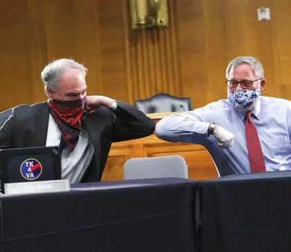 Sen. Tim Kaine, D-Va., left, and Sen. Richard Burr, R-N.C., greet each other with an elbow bump before the Senate Committee for Health, Education, Labor, and Pensions hearing, Tuesday, May 12, 2020 on Capitol Hill in Washington. Dr. Anthony Fauci, director of the National Institute of Allergy and Infectious Diseases, is to testify before the committee.  (Win McNamee/Pool via AP)