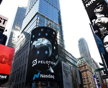 The Peloton logo is displayed, center, on the Nasdaq MarketSite, Thursday, Sept. 26, 2019 in New York's Times Square. (AP Photo/Mark Lennihan)