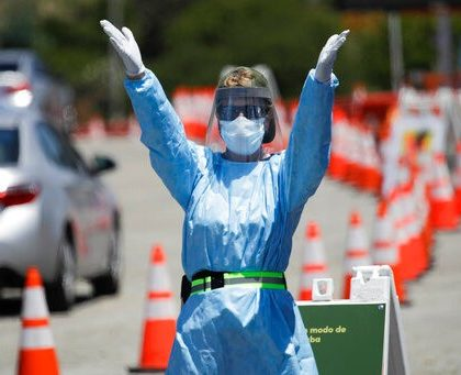 A worker directs traffic at a coronavirus testing site set up at Dodger Stadium Tuesday, May 26, 2020, in Los Angeles. (AP Photo/Marcio Jose Sanchez)
