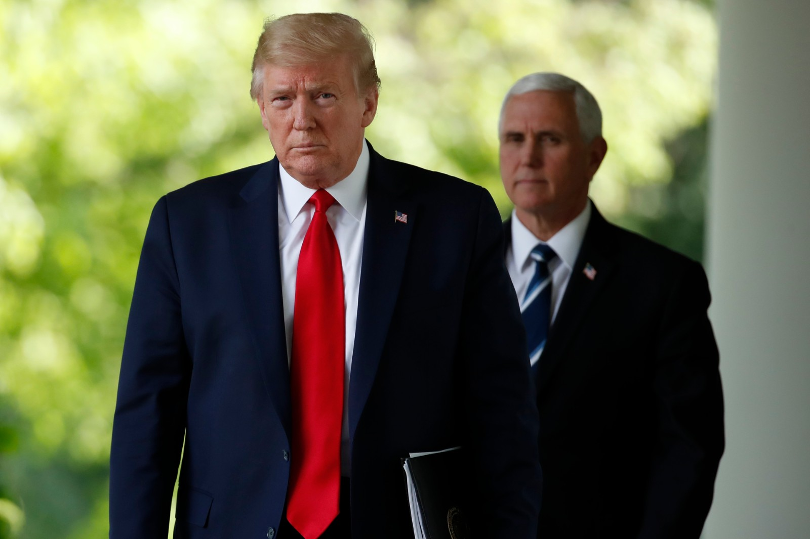 President Donald Trump and Vice President Mike Pence walk from the Oval Office to speak about the coronavirus in the Rose Garden of the White House, Monday, April 27, 2020, in Washington. (AP Photo/Alex Brandon)