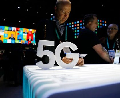 People loook at 5G phones at the Samsung booth during the CES tech show, Tuesday, Jan. 7, 2020, in Las Vegas. (AP Photo/John Locher)