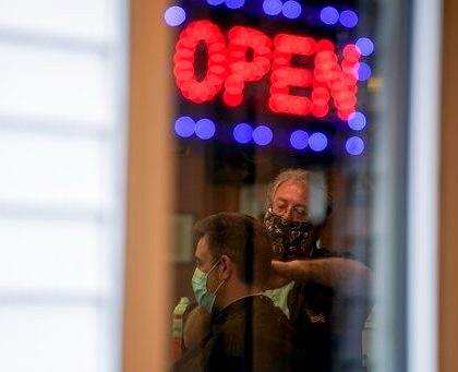 Owner Paul Furrer cuts the hair of Jeff Jones at Rick's Barber Shop Thursday, May 14, 2020, in Waukesha, Wis. The store re-opened after the Wisconsin Supreme Court struck down Gov. Ever's stay-at-home order on Wednesday. (AP Photo/Morry Gash)