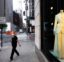 A woman wearing a mask walks by Bergdorf Goodman store, Thursday, June 11, 2020, in New York's Fifth Avenue shopping district. The luxury goods store is open for curbside pickup. (AP Photo/Mark Lennihan)