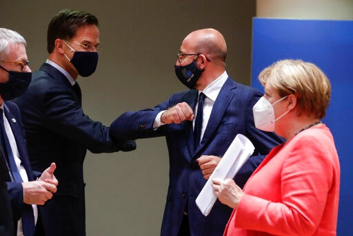Dutch Prime Minister Mark Rutte, center left, elbow bumps with European Council President Charles Michel, center right, as German Chancellor Angela Merkel, right, walks by during a round table meeting at an EU summit in Brussels, Tuesday, July 21, 2020. Weary European Union leaders are expressing cautious optimism that a deal is in sight as they moved into their fifth day of wrangling over an unprecedented budget and coronavirus recovery fund. (Stephanie Lecocq, Pool Photo via AP)