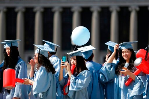 Graduates find their seats during the Columbia University graduation ceremony in New York, Wednesday, May 17, 2017. Over 14,000 students graduated during the ceremonies. (AP Photo/Seth Wenig)