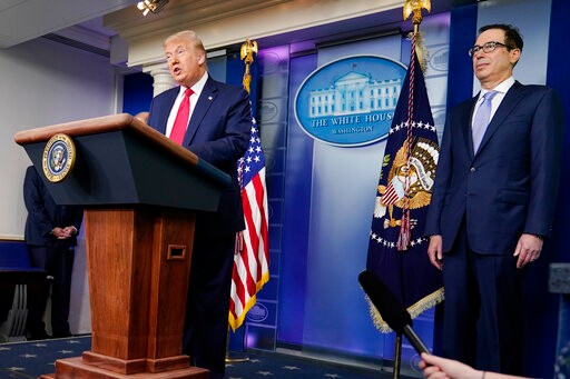 President Donald Trump speaks during a news briefing at the White House, Thursday, July 2, 2020, in Washington, as Treasury Secretary Stephen Mnuchin looks on. (AP Photo/Evan Vucci)