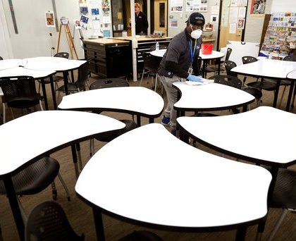 Des Moines Public School employee Sam Teah sanitizes a desk in a classroom at Central Campus high school, Thursday, March 19, 2020, in Des Moines, Iowa. All Des Moines public schools are closed in response to the coronavirus outbreak. (AP Photo/Charlie Neibergall)
