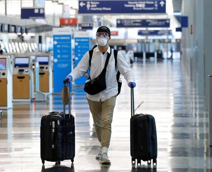 A traveler wears a mask and protective goggles as he walks through Terminal 3 at O'Hare International Airport Tuesday, June 16, 2020, in Chicago. Beginning June 16 at American Airlines and June 18 at United Airlines, all passengers and crew members will be required to wear masks to prevent the spread of COVID-19 pandemic. (AP Photo/Nam Y. Huh)