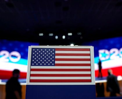 The American flag on top a of state name sign near the stage where Democratic vice presidential candidate Sen. Kamala Harris, D-Calif., will speak on third day of the Democratic National Convention, Wednesday, Aug. 19, 2020, at the Chase Center in Wilmington, Del. (AP Photo/Carolyn Kaster)
