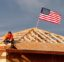 "The American flag flutters in the wind as work is done on the roof of a building under construction in Sacramento, Calif., Tuesday, March 31, 2020. While most Californian's have spent more than a week under a mandatory stay-at-home order, because of the coronavirus, construction work is among the jobs exempt as part of the ""essential infrastructure."" (AP Photo/Rich Pedroncelli)"