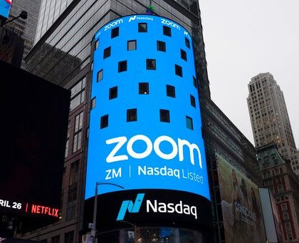 FILE - This April 18, 2019, file photo shows a sign for Zoom Video Communications ahead of the company's Nasdaq IPO in New York. Now that Zoom has emerged as one of the most popular ways to get together virtually while the coronavirus pandemic keeps people apart, the company is trying to build a more secure fortress around the billions of conversations occurring on its videoconferencing service daily. (AP Photo/Mark Lennihan, File)
