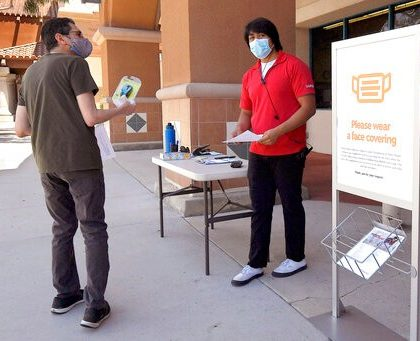 Staples employee Mark Amezcua, center, assists a customer during the coronavirus outbreak, Thursday, May 7, 2020, in Westlake Village, Calif. California Gov. Gavin Newsom has issued the broadest loosening of his stay-at-home order so far, allowing some retailers to reopen but not have customers in stores. (AP Photo/Mark J. Terrill)