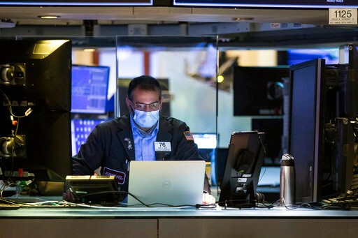 In this photo provided by the New York Stock Exchange, trader Aman Patel wears a protective face mask as he works on the partially reopened trading floor, Tuesday, May 26, 2020. Stocks surged on Wall Street in afternoon trading Tuesday, driving the S&P 500 to its highest level in nearly three months, as hopes for economic recovery overshadow worries about the coronavirus pandemic. (Colin Zimmer/New York Stock Exchange via AP)