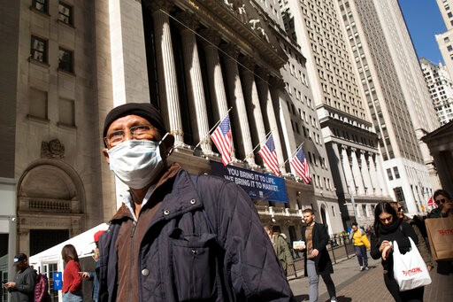 A man wears a mask as he passes the New York Stock Exchange, Monday, March 9, 2020. The dizzying action in financial markets escalated Monday as stocks moved closer to a bear market and oil prices fell the most since 2008. (AP Photo/Mark Lennihan)