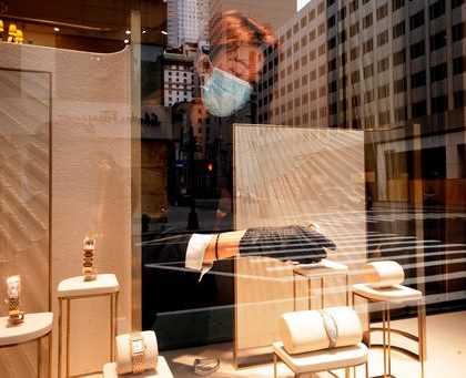 A Cartier employee places a watch in a window display, Thursday, June 11, 2020, in New York's Fifth Avenue shopping district. The jeweler is open for pickup only. (AP Photo/Mark Lennihan)