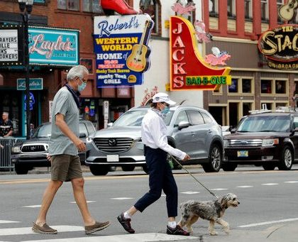 People wear masks as they cross Broadway Tuesday, June 30, 2020, in Nashville, Tenn. The Nashville Health Department has put in place a mask mandate to help battle the spread of the coronavirus. (AP Photo/Mark Humphrey)