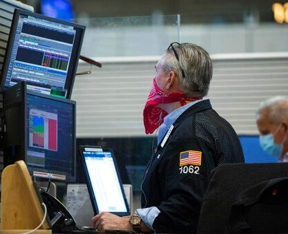 In this photo provided by the New York Stock Exchange, trader Eric Schumacher wears a bandana face mask as he works on the partially reopened trading floor, Tuesday, May 26, 2020, in New York. Stocks surged on Wall Street in afternoon trading Tuesday, driving the S&P 500 to its highest level in nearly three months, as hopes for economic recovery overshadow worries about the coronavirus pandemic. (Colin Zimmer/New York Stock Exchange via AP)