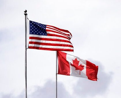 In this photo taken Sunday, May 17, 2020, U.S. and Canadian flags fly atop the Peace Arch at Peace Arch Historical State Park on the border with Canada, where people can walk freely between the two countries at an otherwise closed border, in Blaine, Wash. Canada and the U.S. have agreed to extend their agreement to keep the border closed to non-essential travel to June 21 during the coronavirus pandemic. The restrictions were announced on March 18, were extended in April and now extended by another 30 days. (AP Photo/Elaine Thompson)
