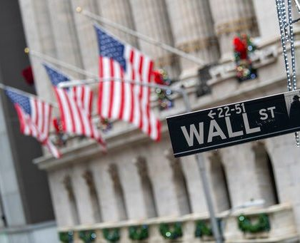 The Wall St. street sign is framed by American flags flying outside the New York Stock Exchange, Friday, Jan. 3, 2020, in New York. Stocks fell broadly on Wall Street in midday trading Friday and oil prices surged after U.S. forces in Iraq killed a top Iranian general. (AP Photo/Mary Altaffer)