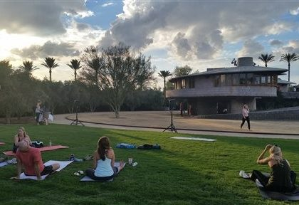 In this Tuesday, Sept. 22, 2015 photo, Participants get ready for a free yoga class outside the David and Gladys Wright House in Phoenix.  The Frank Lloyd Wright-designed Phoenix home will temporarily cease hosting daily tours and special events after May 7. Operators want to focus on finding organizations to collaborate on preservation and operations plans. (AP Photo/Terry Tang)