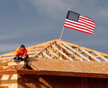 """The American flag flutters in the wind as work is done on the roof of a building under construction in Sacramento, Calif., Tuesday, March 31, 2020. While most Californian's have spent more than a week under a mandatory stay-at-home order, because of the coronavirus, construction work is among the jobs exempt as part of the """"essential infrastructure."""" (AP Photo/Rich Pedroncelli)"""
